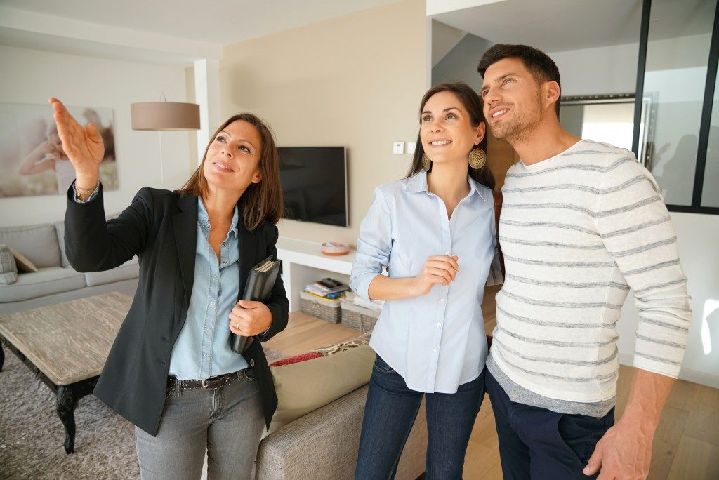 broker showing couple around the unit for sale