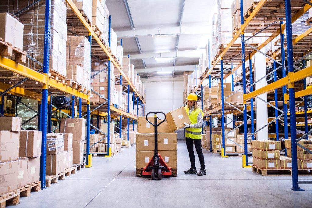 Woman loading boxes in warehouse