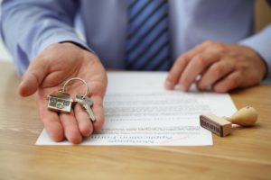 Key with house keychain being handed with mortgage form