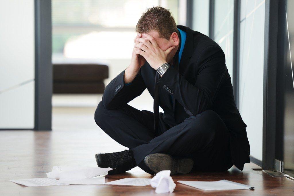 Stressed businessman sitting on the floor