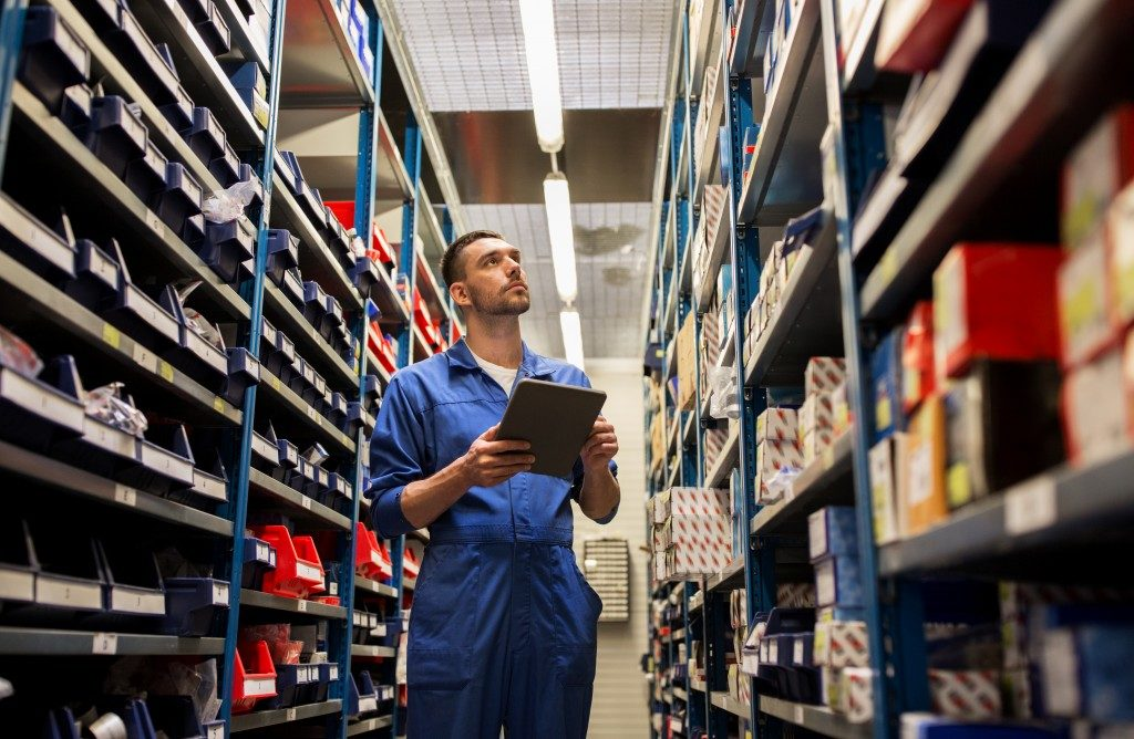 Male warehouse worker checking shelves