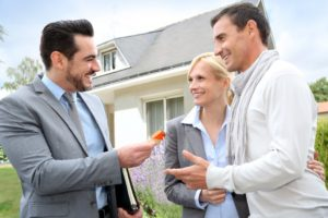 Real estate agent giving keys to couple