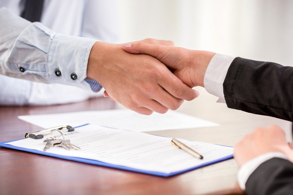 Real estate agent shaking hands with the client