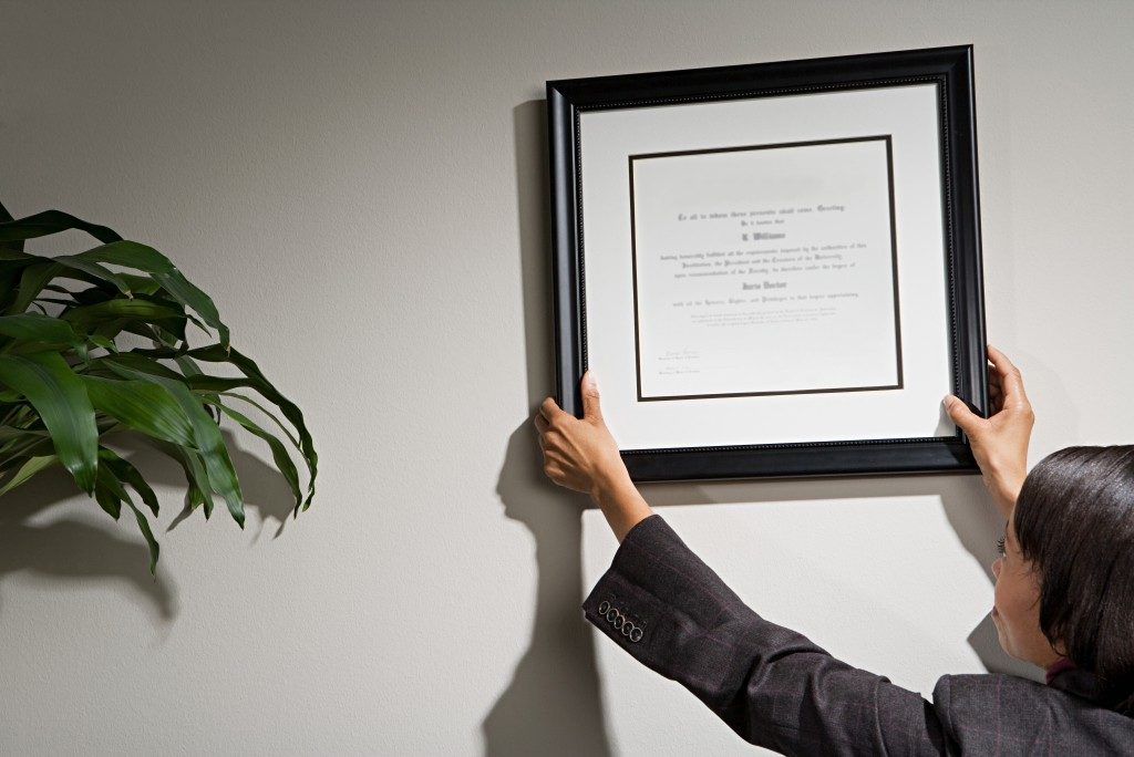 Business woman hanging framed certificate