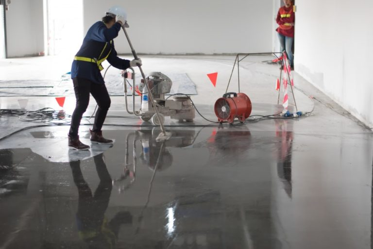 person cleaning concrete floors