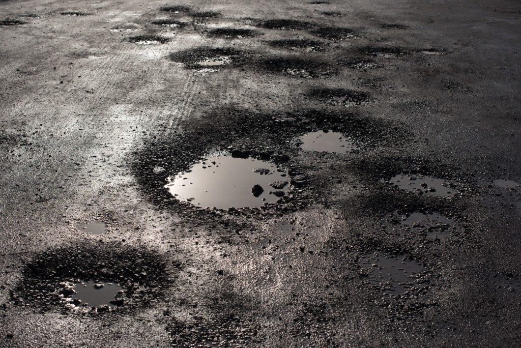 potholes in the road looking like alien craters