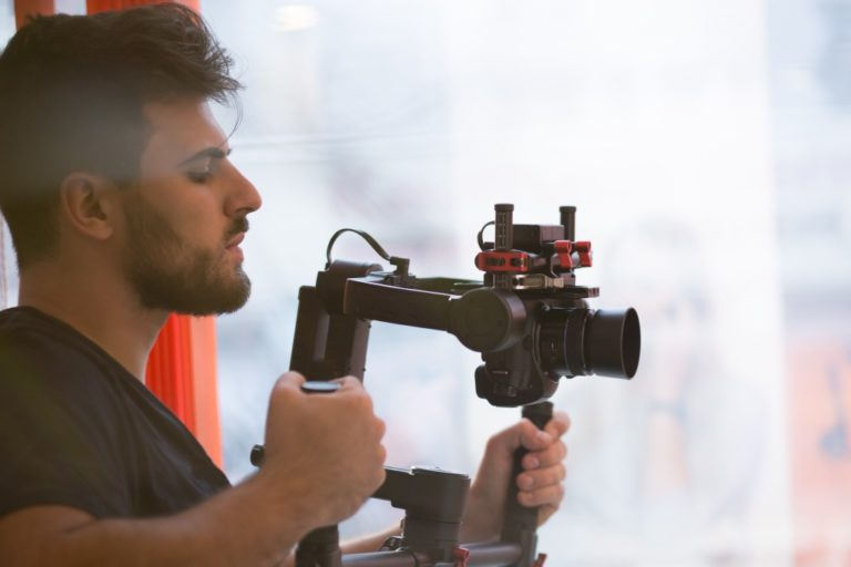 man filming with his camera