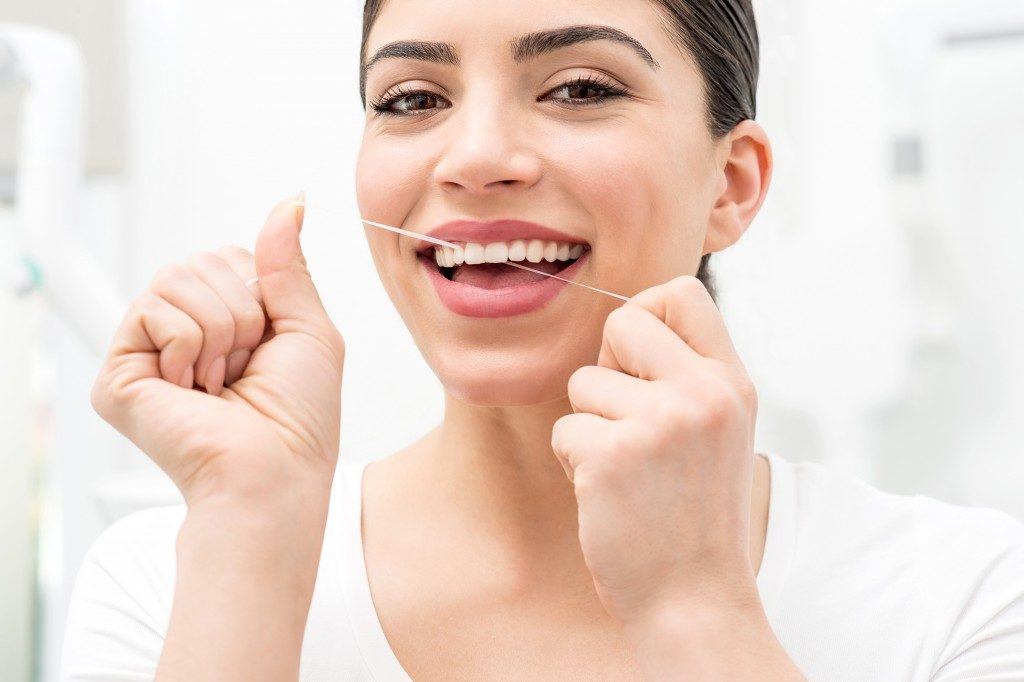 Woman using dental floss for cleaning her teeth