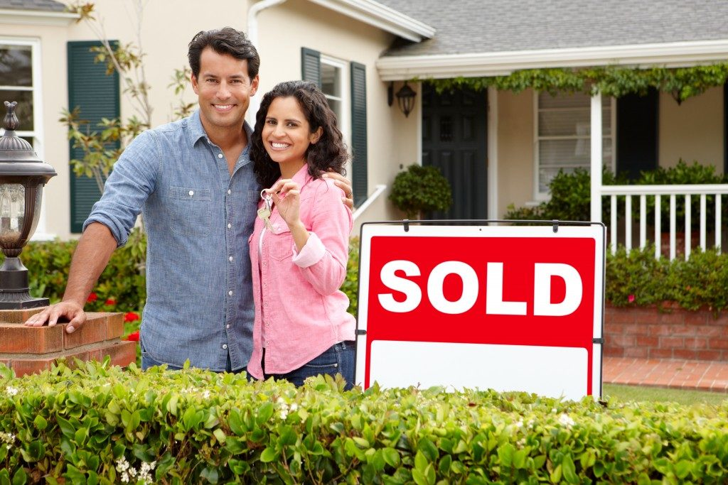 couple outside home with sold sign