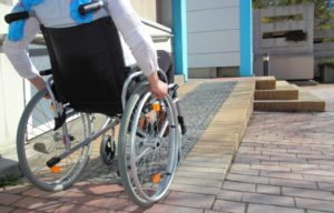 Person with disability on a wheelchair ramp