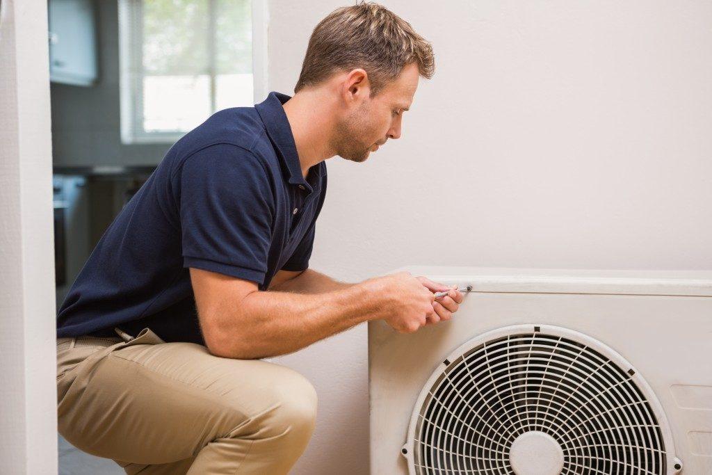 man repairing air conditioning system