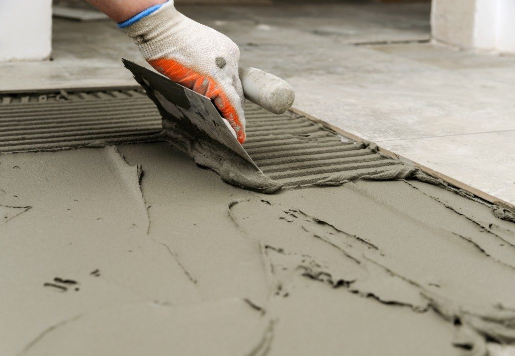 Troweling mortar onto a concrete floor