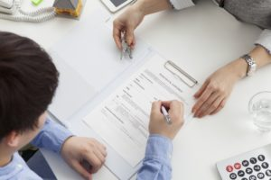 Man signing contract of land sale