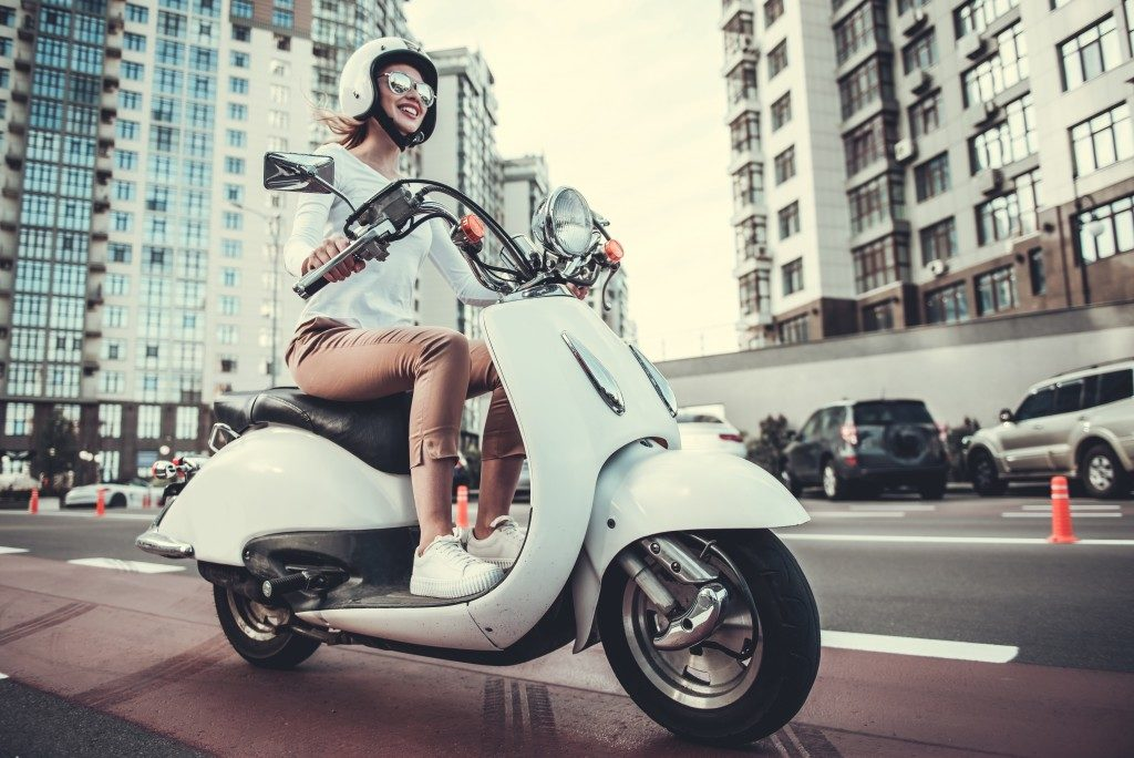 Female riding a white motorcycle in the city
