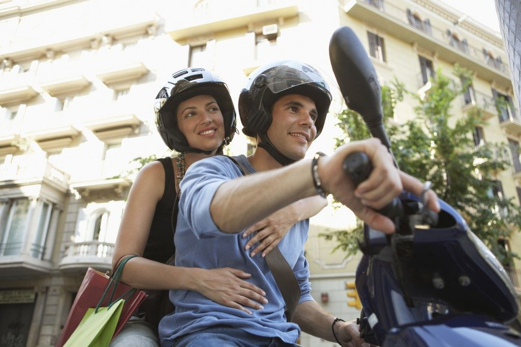 Young couple smiling while enjoying road trip on scooter