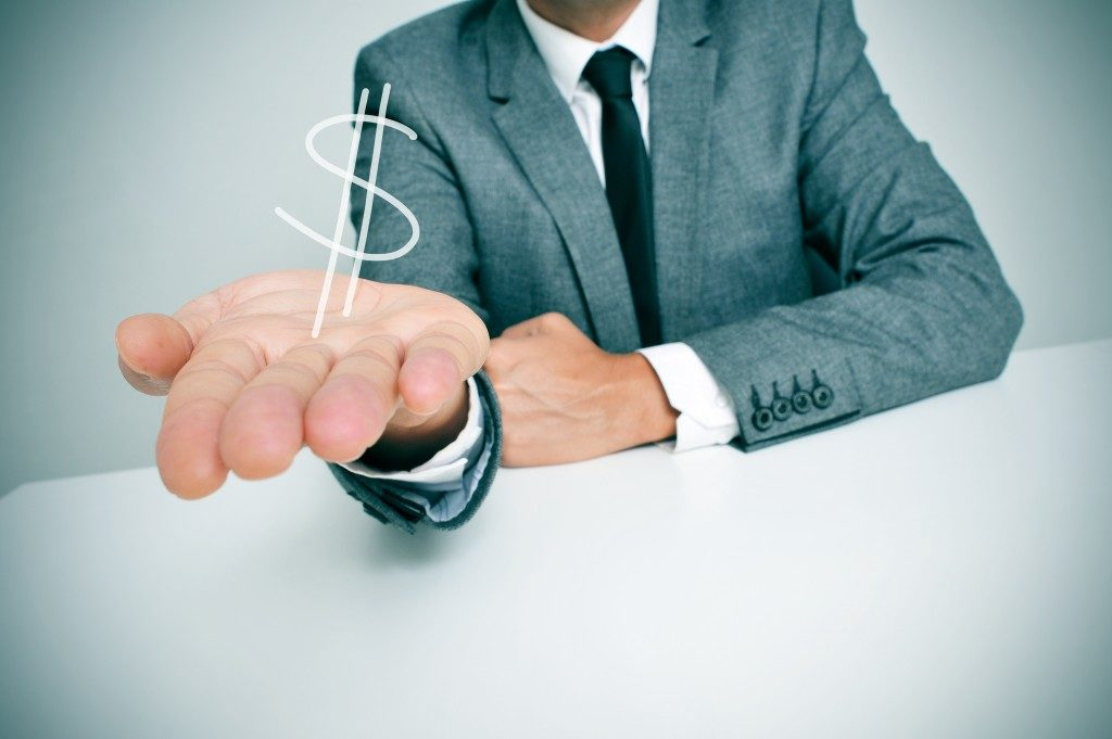 man showing a dollar sign on his hand