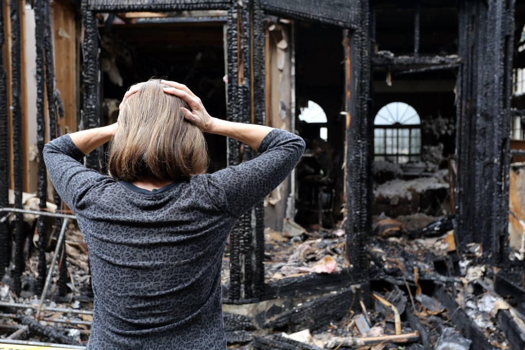 woman looking at a burned down house