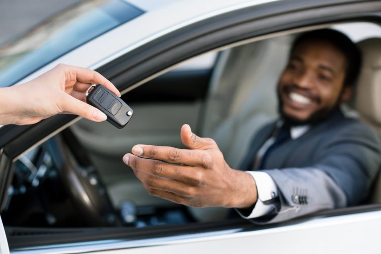 Professional salesperson giving keys to new car owner