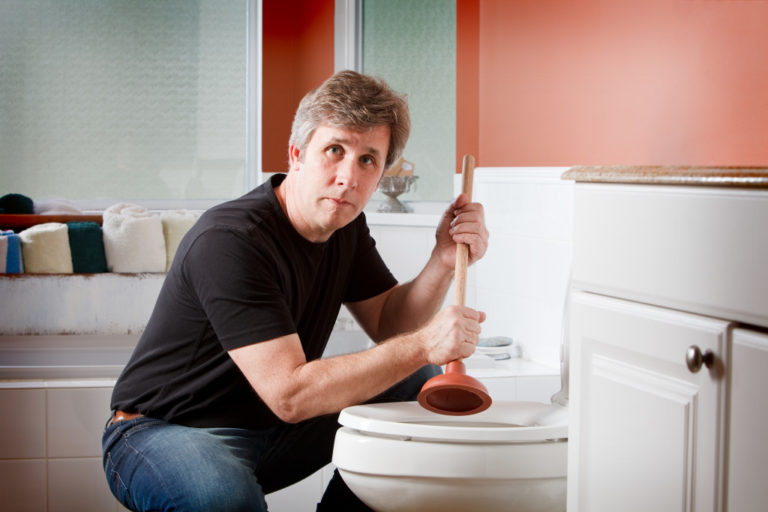 man fixing a clogged toilet