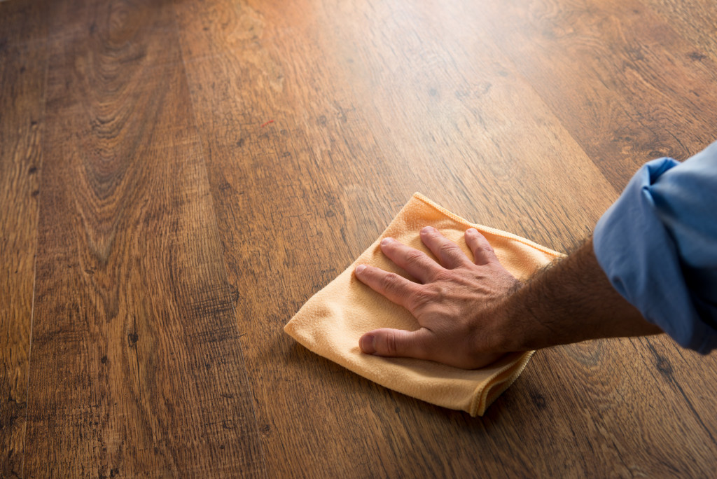 Cleaning and rubbing an hardwood floor with a microfiber cloth