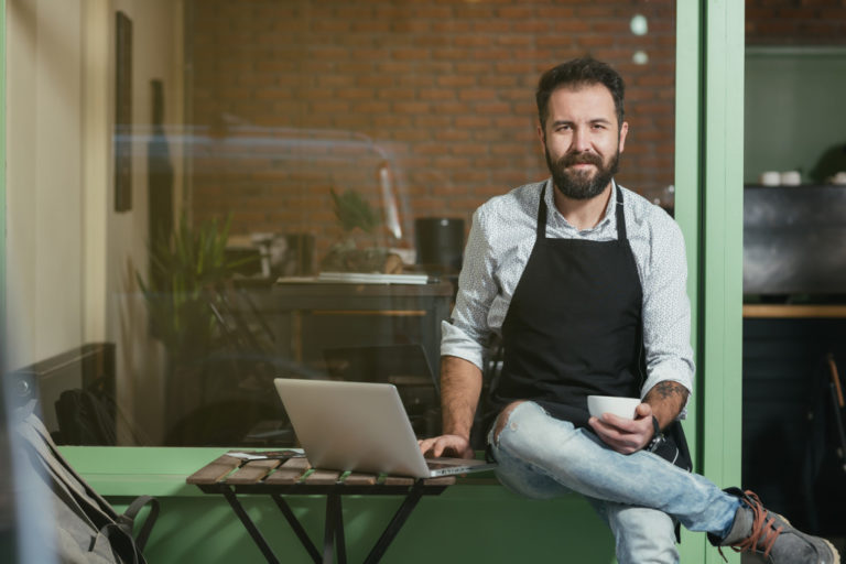 barista with coffee and laptop